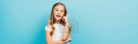 Photo for Horizontal image of excited girl in white t-shirt showing idea sign while looking at camera isolated on blue - Royalty Free Image