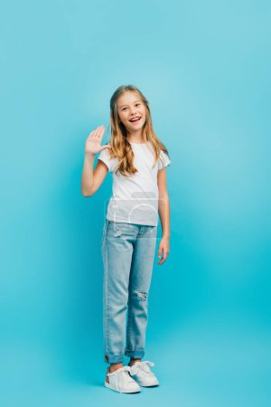 full length view of girl in white t-shirt and jeans waving hand while looking at camera on blue
