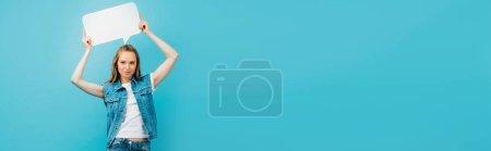Photo pour Concept panoramique de jeune femme en gilet en denim tenant bulle de discours au-dessus de la tête isolé sur bleu - image libre de droit