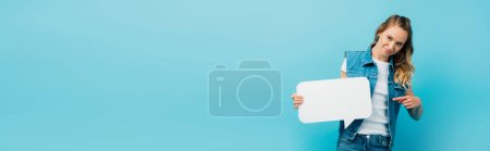 Photo for Horizontal image of young woman in denim vest pointing with finger at speech bubble isolated on blue - Royalty Free Image