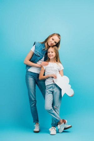 Photo for Full length view of young woman in denim clothes touching daughter holding thought bubble on blue - Royalty Free Image