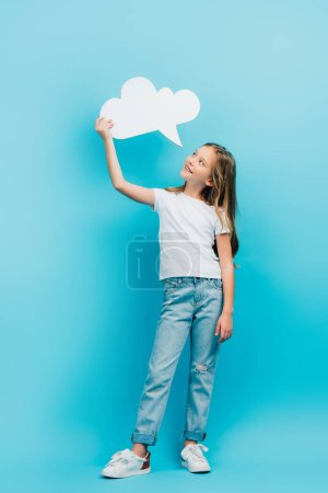 full length view of girl in white t-shirt and blue jeans holding thought bubble on blue