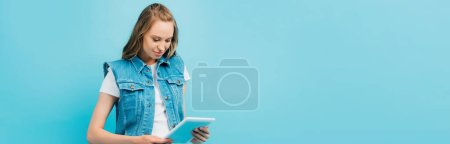Photo for Horizontal image of concentrated woman in denim vest using digital tablet isolated on blue - Royalty Free Image