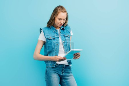 focused woman in denim clothes using digital tablet isolated on blue