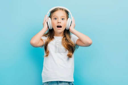 excited girl in white t-shirt touching wireless headphones while looking at camera isolated on blue