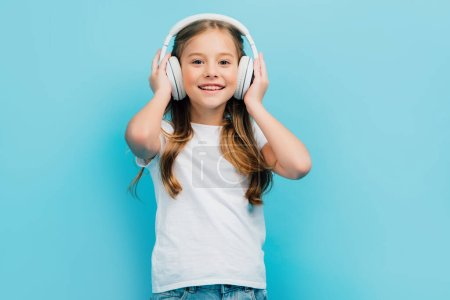 Photo for Girl in white t-shirt touching wireless headphones while looking at camera isolated on blue - Royalty Free Image