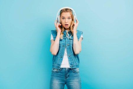 Photo pour Femme choquée en vêtements en denim touchant écouteurs sans fil tout en regardant la caméra avec la bouche ouverte isolé sur bleu - image libre de droit