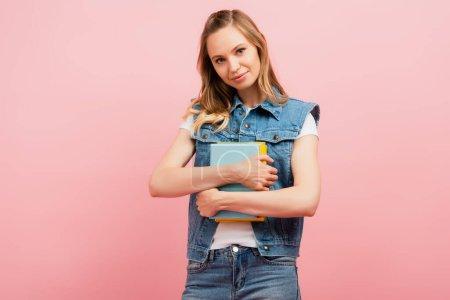 Photo pour Jeune femme en denim tenant des livres et regardant la caméra isolée sur rose - image libre de droit