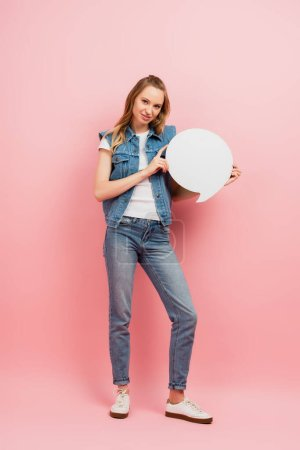 full length view of young woman in denim clothes holding thought bubble and looking at camera on pink