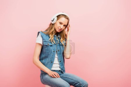 young woman in denim clothes touching wireless headphones while sitting isolated on pink and looking at camera