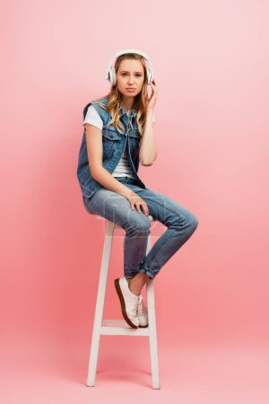 serious woman in denim clothes touching wireless headphones while sitting on high stool on pink