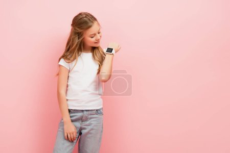 kid in white t-shirt and jeans looking at smartwatch isolated on pink