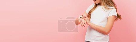 Teilansicht des Kindes im weißen T-Shirt, das die Smartwatch berührt, isoliert auf rosa, panoramisches Konzept