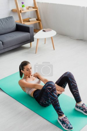 High angle view of brunette sportswoman training on fitness mat at home