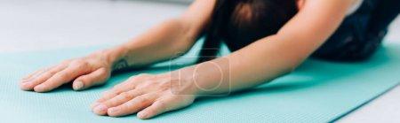 Récolte horizontale de sportive étirant sur tapis de fitness
