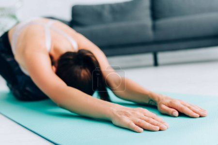 Photo for Selective focus of sportswoman stretching after work out on fitness mat at home - Royalty Free Image