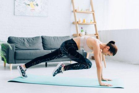 Photo pour Side vie of fit sportswoman exercising in living room - image libre de droit