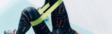Photo pour Image panoramique d'une sportive s'entraînant avec une bande de résistance sur les jambes à la maison - image libre de droit