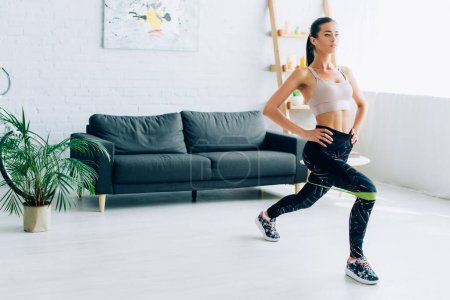 Photo for Young sportswoman doing lunges with resistance band at home - Royalty Free Image
