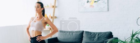 Panoramic shot of brunette sportswoman with hands on hips looking away in living room