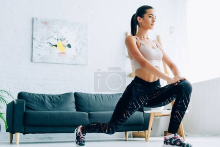 Fit sportswoman doing lunges during training at home