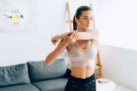 Young brunette sportswoman stretching arms at home