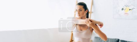 Photo for Panoramic orientation of brunette sportswoman stretching arms in living room - Royalty Free Image