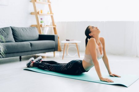 Photo for Selective focus of fit sportswoman stretching back on fitness mat at home - Royalty Free Image