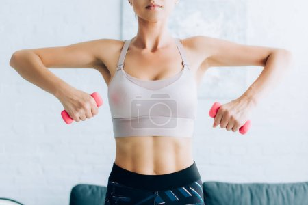 Photo for Cropped view of fit sportswoman holding dumbbells while exercising at home - Royalty Free Image