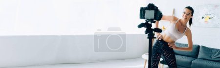 Photo pour Prise de vue panoramique d'une sportive en forme regardant un appareil photo numérique sur un trépied pendant son entraînement à la maison - image libre de droit