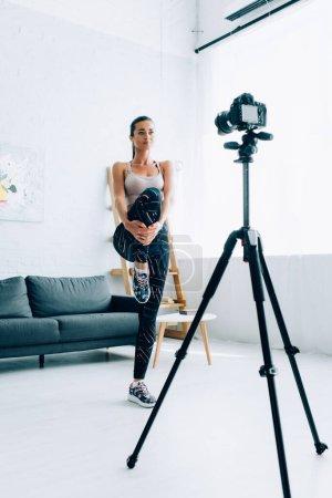 Photo pour Focus sélectif de la sportive brune qui se réchauffe avant de s'entraîner près de l'appareil photo numérique à la maison - image libre de droit