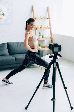 Selective focus of sportswoman doing lunges with resistance band and looking at digital camera at home
