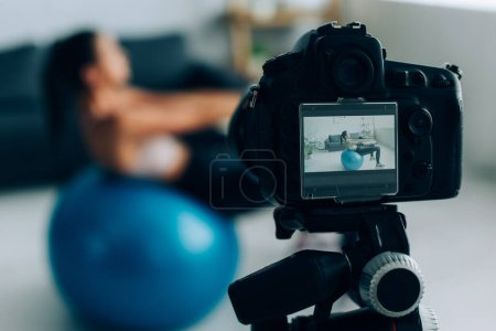 Selective focus of digital camera near sportswoman working out with fitness ball in living room
