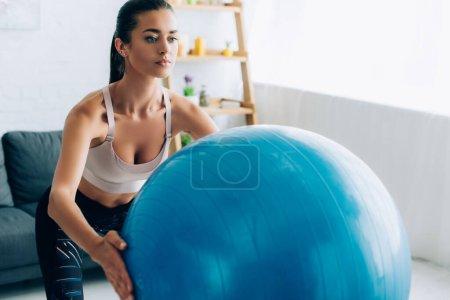 Photo pour Concentration sélective de la jeune sportive tenant le ballon de remise en forme tout en faisant squat dans le salon - image libre de droit