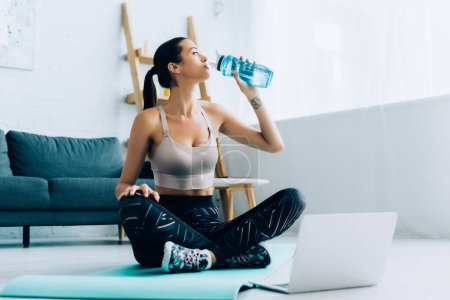 Photo for Selective focus of sportswoman drinking water while sitting on fitness mat near laptop - Royalty Free Image