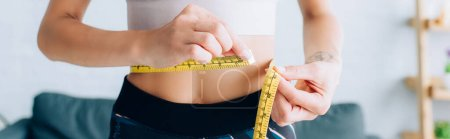 Photo for Panoramic crop of fit sportswoman measuring waist at home - Royalty Free Image