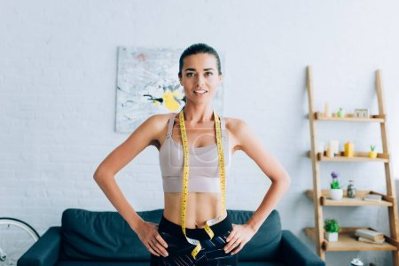 Photo for Fit sportswoman with measuring tape around neck and hands on hips looking at camera - Royalty Free Image