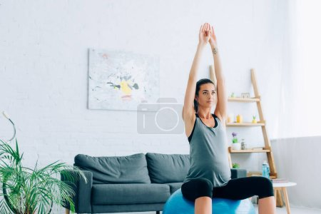Young pregnant sportswoman training on fitness ball in living room