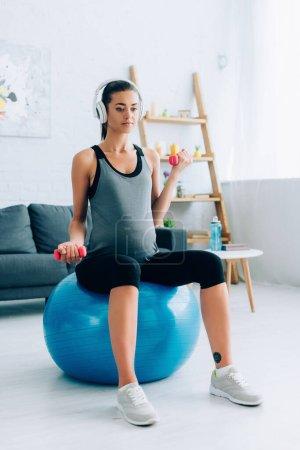 Photo pour Femme sportive enceinte dans un casque d'entraînement avec haltères et balle de remise en forme à la maison - image libre de droit