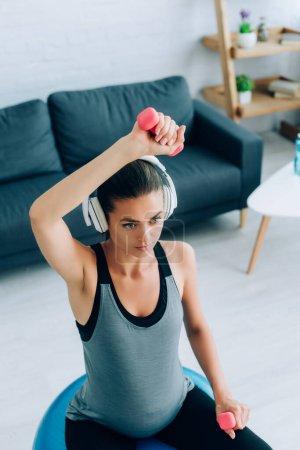 Photo pour Concentration sélective de la femme enceinte dans les écouteurs de travail avec haltères et balle de remise en forme dans le salon - image libre de droit
