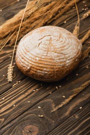 Photo pour Foyer sélectif de pain blanc cuit au four frais avec des épillets sur la surface en bois - image libre de droit