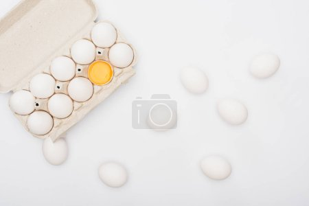 Photo for Top view of fresh chicken eggs and yolk in cardboard box isolated on white - Royalty Free Image