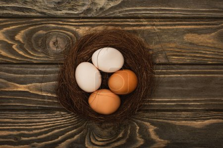 Photo for Top view of fresh chicken eggs in nest on wooden surface - Royalty Free Image