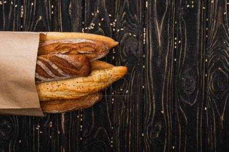 vue du dessus des pains de baguette frais cuits au four dans un sac en papier sur une surface noire en bois