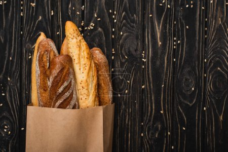 Photo for Top view of fresh baked baguette loaves in paper bag on wooden black surface - Royalty Free Image