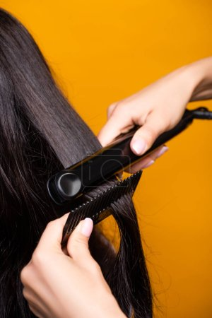 Photo pour Vue recadrée du coiffeur à l'aide d'un lisseur et d'un peigne isolés sur jaune - image libre de droit