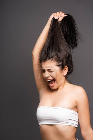 Photo pour Upset brunette woman holding damaged hair and yelling isolated on black - image libre de droit
