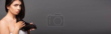 Photo pour Bouleversé brunette femme toucher cheveux isolés sur noir, panoramique shot - image libre de droit
