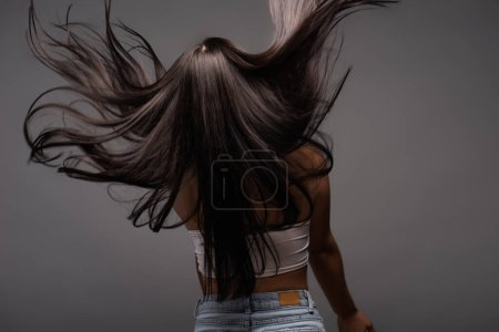 Photo pour Back view of brunette long haired woman isolated on black - image libre de droit