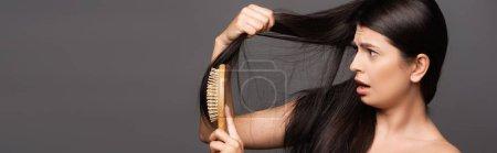 Photo pour Nu choqué brunette femme brossage cheveux isolé sur noir, panoramique shot - image libre de droit